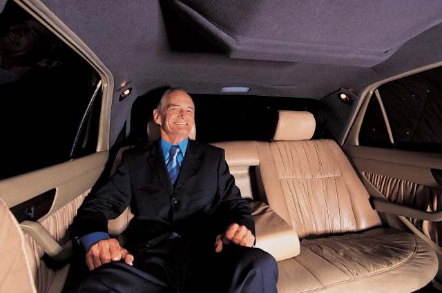 Senior Businessman Sitting in the Back Seat of a Limousine