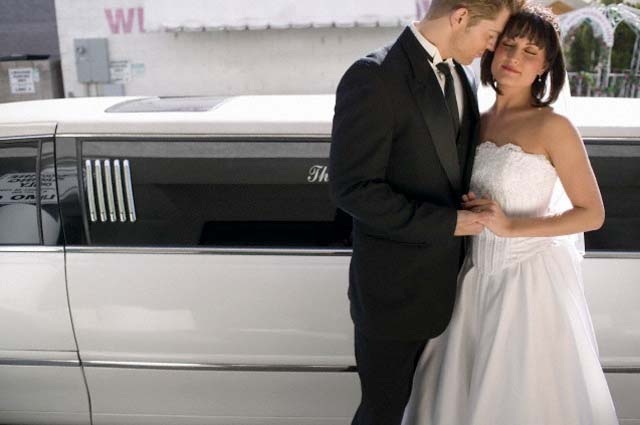 Bride and Groom Standing Together in Front of a Stretch Limousine